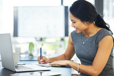 Cropped shot of a young businesswoman writing notes while working on a laptop in a modern office