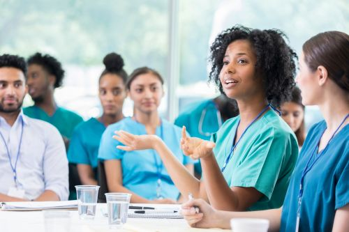 Confident female doctor gestures while answering a colleagues question during healthcare conference. She is participating in a panel discussion. The audience is in the background.