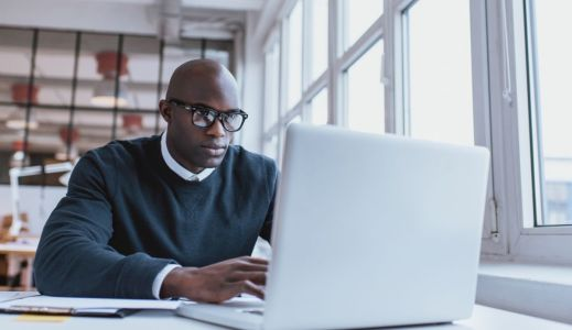 Shot of a bald african businessman working on laptop computer in office. Young web designer sitting at his desk working.