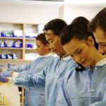Four laboratory technicians in hospital processing specimens